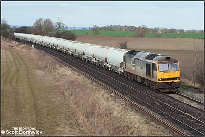 60064 is pictured at Portway, north of Tamworth, on 18/02/2005 whilst working a heavilly delayed 6M09 0245 Tunstead Sdgs-Walsall. The delay enabled this daytime photo of an otherwise nocturnal working.