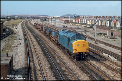 An unidentified class 37 passes Cardiff Canton TMD with a short trainload of steel coil on 03/05/1986.