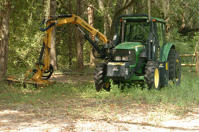 Tractor with mower head helps reach off-camber areas.