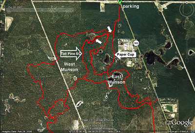"""20 May 2010 map Map created by combining this and this GPS track. From parking area, entrance trail has been revised. Uppermost white arrow indicates where entrance now takes you up to the Tall Pine Shortcut/Munson north bench intersection. It makes more sense, and takes pressure off Paper Cup Trail. Some concern has been indicated about the section of PC passing between two ponds. That section of PC may be closed. Other small white arrow indicates major reroute on Tall Pine Shortcut. As of 20 May, all work has been restricted to the East """"side"""" of Munson, using TPS as the divider between East and West. Twilight Zone Trail is south of this map, with East and West Connectors partially shown. Got all that?"""