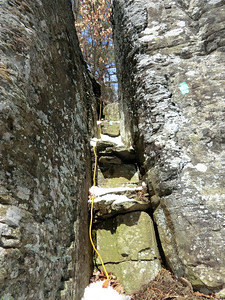 Squeezer while climbing up the Middleburgh Cliffs (3-21-13). Yellow cable is electrical cord for holiday lights!