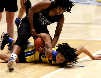 Photo by Matt Griffith/VU  Vincenenes University's Trinitee Harris, on floor, reaches back to try to control the ball away from Shawnee's 23, Monday night in the P.E. Complex.