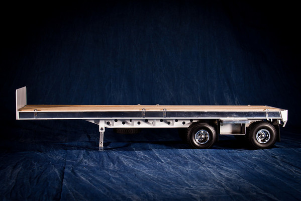 Features of the Flatbed Trailer includes headboard, red oak deck, polished aluminum strips on either side of the deck, tie-down brackets, spare tire spread axle, tarp boxes with polished aluminum doors, custom wheels, mudflaps, heavy bumper, landing gear, detailed undercarriage with braces, 5th wheel socket or pin, tail light bezel with reflectors; welded steel construction using laser cut and machined steel parts.