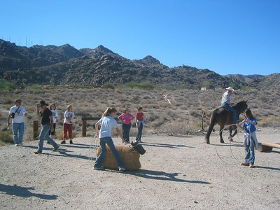 Wranglers showing girls how to rope a calf.