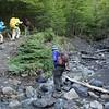 Sue is crossing a stream near Refuge Chileano, where we took a snack break.