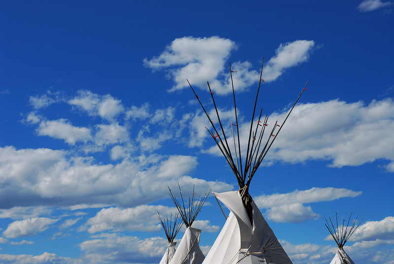 Tepees in the wind with blue sky and clouds.<br />   Taken at the  Aurora colorado, Plains Conservation Center