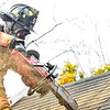 KRISTOPHER RADDER — BRATTLEBORO REFORMER<br /> Brattleboro firefighter Will Streeter uses a chainsaw to cut into a roof during training at Melrose Terrace on Monday, Oct. 28, 2019.