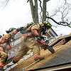 KRISTOPHER RADDER — BRATTLEBORO REFORMER<br /> On his first day on the job, Brody Burke, a Brattleboro firefighter, cuts a hole into a roof as firefighter Will Streeter supports him during a ventilation training at Melrose Terrace on Monday, Oct. 28, 2019.