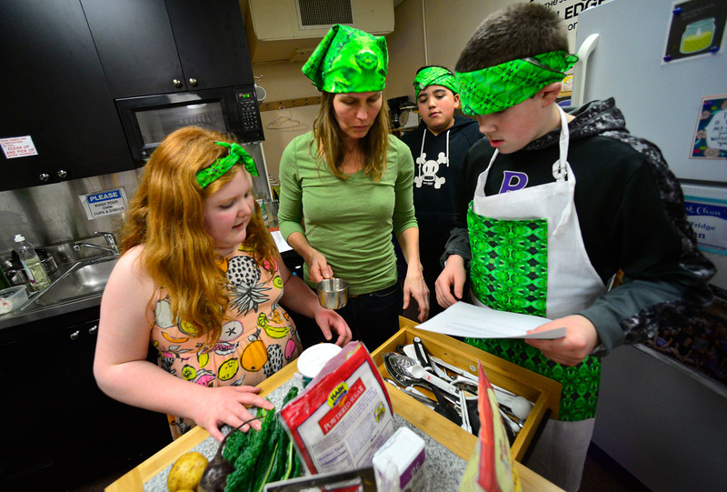 KRISTOPHER RADDER — BRATTLEBORO REFORMER<br /> Jeriah Easton, Jayson Tirrell and Alex Aither, students at Green Street School, go over the recipe with Tara Gordon as they train for the Junior Iron Chef state competition on Wednesday, Feb. 27, 2020.