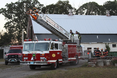 Firefighters Doug DeCesare, Tom Steele, and Jason Fischer practice Aerial Ladder Operations.