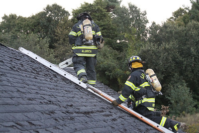 Firefighters Ryan Aldrich and Mark Cutler practice roof ladder and ventilation techniques.