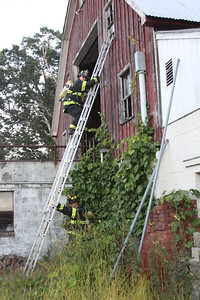 Firefighter David Peets practices a ladder climb and window ventilation while firefighter Mike McGovern secures the ladder.