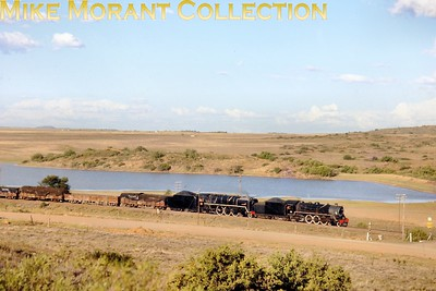 """South African steam railways - Orange Free State System. An unidentified Henschel-built South African Railways 16DA-class """"wide-firebox"""" 4-6-2 pilots 16E class Pacific locomotive No. 857 Vereeniging with a fast freight in the southern Orange Free State in 1973. No. 857 had also been built by Henschel & Sohn [under works number 22586/1935]. [A.E. """"Dusty"""" Durrant / Mike Morant collection]"""