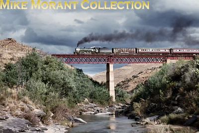 """South African steam railways - Cape Eastern sytem. An SAR class 19D 4-8-2 locomotive heads a Sterkstroom to Maclear passenger train, crossing the Tsomo River bridge near Cala Road - 1974/5. [A.E. """"Dusty"""" Durrant / Mike Morant collection]"""