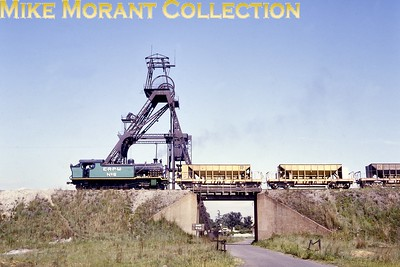 """South African industrial steam railways East Rand Proprietary Mines 3' 6"""" gauge 4-8-4T locomotive - ERPM No. 6 - hauls a string of ore hoppers past mineshaft headgear at Boksburg in 1981. It had been built by the North British Locomotive Company [under its Hyde Park (Glasgow) works number 25901/1946] and had operated as ERPM No. 5 before receiving a major overhaul by Dunns in 1980. [A.E. """"Dusty"""" Durrant / Mike Morant collection]"""