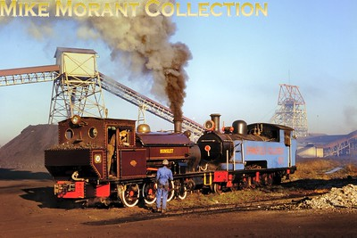 """South African industrial steam railways Standing in for one of the mine's own locomotives, ESCOM (Electricity Supply Commission) 2-6-0ST Hunslet [HE 790/1902] - from the nearby Grootvlei Power Station (Southern Transvaal) - shunts Springfield Colliery's 4-8-2T No. 2 in 1980. Previously at Daggafontein Mines near Springs, the ex-South African Railways G-class locomotive [No. 206] had been built by the North British Locomotive Company [under works number 16069/1904] for the Natal Government Railways - and first entered service as NGR B-class No. 259. [A.E. """"Dusty"""" Durrant / Mike Morant collection]"""