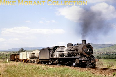 """Swaziland Railways. South African Railways class 15AR 4-8-2 locomotive No. 2080 (on hire to Swaziland Railways) heads a general freight train near Matsapha in 1980. It had been built by J.A. Maffei [under Munich works number 5625/1925]. [A.E. """"Dusty"""" Durrant / Mike Morant collection]"""