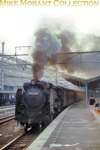 Japan Railways JNR light Pacific No. D51.1054 leaving Kyoto station with the last Hiroshima stopping train of the day on an unspecified date in 1966.  [Photographer: R. E. Field/Mike Morant collection]