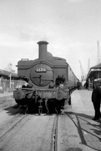 GWR Collett outside cylindered 0-6-0PT No. 1370 of the 1366 class is depicted here at Weymouth's Quay station in August 1956. Of this small class of only six locomotives No. 1370 had the dubious distinction of being the first to be withdrawn, from Weymouth mpd, in January 1960. Fortunately, classmate No. 1369 fared somewhat better and has survived into the heritage era.