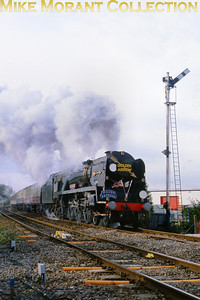 The preservd Bulleid rebuilt West Country pacific no. 34027 Taw Valley accelerates past a splendid semaphore signal at the Queen Adelaide level crossing en route from Cambidge to Kings Lynn durng the splendidly organised 'Fen Line Steam Weekend' of the 19th and 20th October 1991.