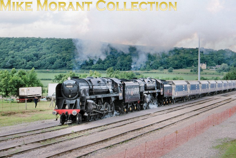 On June 28th 1998 the two preserved Standard 9F 2-10-0's, nos. 92212 and 92203, were put in charge of demontration freights, 1,000 tons of stone in Foster Yeoman hoppers, at FY's Merehead quarry near Cranmore in Somerset. Here we see the pair  nearly at the end of their ascent from Torr quarry.<br> [<i>Slide taken by Mke Morant</i>]