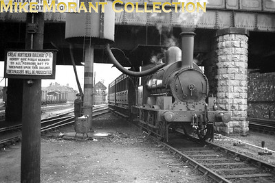 """Vintage Irish Railways - DNGR - Dundalk Newry & Greenore Railway Sometimes a picture contains more detail than can be seen in the image displayed within the eBay environment and this is just such an example thereof.It emanates from the late Bob O'Sullivan's archive and as ever with recycled material there's no supporting data but the probable date of this shot is circa 1947/8. The location is easy to pinpoint as the signal box in the background clearly states that it is Dundalk Central. The locomotive is the Dundalk Newry and Greenore Railway's Ramsbottom 0-6-0ST Special Tank No. 1 named Macrory which was a 5' 3"""" gauge conversion from the standard Crewe product of 1873. I believe, also, that the visible rolling stock attached to the engine was also of LNWR design and that it is still in LNWR livery but that isn't clear in this picture.There's more of interest in this picture taken as the loco imbibes from the water crane. The trucks at the left of shot proclaim their GNR(I) origins whilst the cast iron trespassers notice in the foreground does the same. The water column has a substantial leakage which appears to be describing a perfect arc directly into the engine's cab whilst one has to wonder about safety rules as the rolling stock is clearly fouling pointwork on what seems to be well used track. [Mike Morant collection]"""