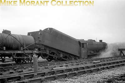 """LMSR Stanier 8F 2-8-0 no. 48512 in a bit of a pickle. I bought this negative from the photographer who kindly provided his personal notes: """"48512 ran away down the headshunt of Rochdale goods yard down side, which used the trackbed of the Bacup branch, I think this was in 1966 or 1967 but it may have been earlier. Having demolished the buffer stop the 'ballast' stopped further progress, which would have been a steep drop off the abutments of the Roch Valley viaduct and possibly into the river below."""""""