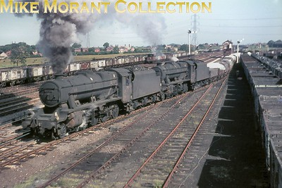 Stanier 8F 2-8-0 no. 48320 and an unidentified classmate double-head a freight train leaving the yard and crossing onto the main line at Farington Junction on 30/6/66. 48320 was alloocated to Lostock Hall when this shot was taken and remained there until withdrawal in march 1967. [Mike Morant collection]
