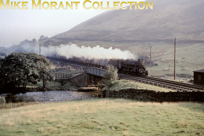 One of those magical steam in the landscape shots that this time depicts a snow plough fitted Stanier Black '5' 4-6-0 racing through the fells at the end of August 1964. The location is just south of Tebay with the A685 immediately behind the camera and depicts an 'up' train in the early morning. So nostalgic without any wires! Thanks are due to Colin Williams, Peter Kellet and Robin Lush for providing the the above notes.