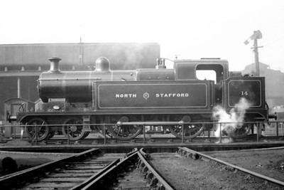 "This side profile of North Staffordshire Railway 'K' class 4-4-2T no. 14 is depicted on a turntable at what the sleeve note describe as Manchester 1921 and which a viewer has confirmed as being London Road. No, 14 was a product of the NSR's Stoke works in June 1912, was renumbered to 2185 and classified as 3P by the LMSR which saw fit to withdraw this handsome engine in December 1933. That same viewer adds this: ""These engines worked London expresses as far as Stoke where LNWR engines took over.  It was all part of the rather complicated arrangements between the two companies after the initial struggle on the part of the NSR to avoid being taken over.  In those balmy days (as they say) the LNWR engine would actually work down light engine from Crewe to Stoke to take over the train and so there certainly wasn't much money saved by this arrangement"""