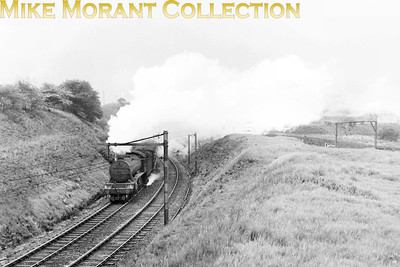 An unidentied Gresley K3 2-6-0 leaves Dinting working 'wrong line' in June 1954. The other shots in this series suggest that it was taken just prior to the start of electric services via Woodhead. There's no doubting the location as witnessed by the large sign near the right side of the image. [Mike Morant collection]