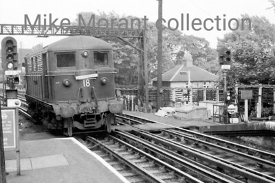 London Transport Metropolitan Vickers built Bo-Bo electric loco No. 18 Michael Faraday at Rickmansworth in April 1958. The loco is moving towards the north of the station and will then reverse along the Up line to the storage facility at the south end. The stock it has left in the station will proceed northwards behind a steam loco that is waiting in the sidings just out of sight of this photo. No. 18 was woithdrawn in 1962 but wouldn't be scrapped until 1966. [Mike Morant]