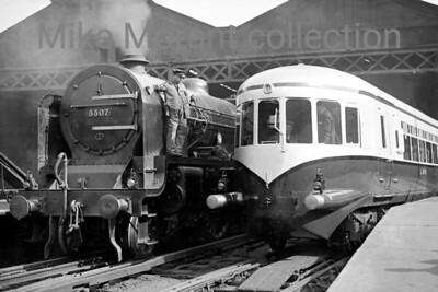 LMSR Fowler 'Patriot' class 4-6-0 no. 5507Royal Tank Corps alongside the LMS's experimental diesel railcar at Euston station on an unspecified date in 1938. The railcar was evidently new when this shot was taken and would become better known for its use on St. Pancras - Nottingham services and then on the varsity line between Oxford and Cambridge. The unit was withdrawn at the outbreak of WW2 in 1939 and would never resurface in this form which was a great shame as it still has a modern look to it even today. Just for the record, 5507 has an 8A Edge Hill shed plate. [Mike Morant collection]
