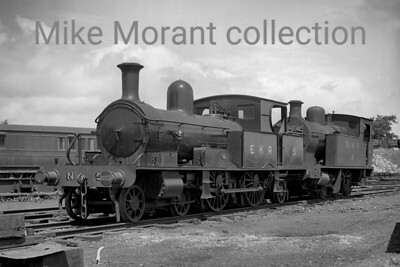 A Col. Stephens railway negative depicting East Kent Railway no. 5 which was its purchased former LSWR Adams 4-4-2 radial tank and posed for the photographer at Shepherdswell on 18/7/1936. There are two distinctly different stories relating to this acquisition one of which is probably Urban Myth and so we'll stick with the Bradley version which is more likely to be the historically accurate one. Originally LSWR no. 488 built by Neilson Reid and delivered in March 1885, this loco was sold out of service to the Ministry of Munitions to which it was delivered under itrs own steam from Eastleigh Works on September 17th, 1919. It was subsequently offered for sale in August 1920, was purchased by Col. Stephens and was then delivered to the EKR in April 1921. No. 5 would subsequently be bought back from the EKR by the Southern Railway in March 1946 specifically to address a motive power shortage on the Axminster to Lyme Regis branchand was correctly renumbered to 3488 becoming BR 30583 in lined black livery during September 1949. Withdrawal came at Exmouth Junction mpd in July 1961 but 30583 was purchased by the Bluebell Railway where it is still periodically active. [H. C. Casserley / Mike Morant collection]