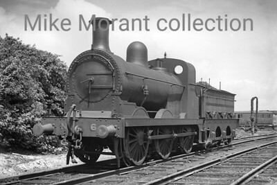 A Col. Stephens railway negative depicting East Kent Railway Wainwright/Stirling 'O1' class 0-6-0 'O1' class no.6 at Shepherdswell on 18/7/1936. No. 6 had been purchased from the Southern Railway in 1923 and was painted in unlined black. The reason that no. 6 appears to be an 'O' class is that a Wainwright 'O1' boiler had been fitted in 1933 but it uniquely retained its original Stirling style of cab. No. 6 was absorbed into BR stock at nationalisation nominally renumbered to 31372 but it was never applied and it was withdrawn in February 1949 not reallocated to a BR depot. [H. C. Casserley / Mike Morant collection]