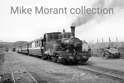 """This very rare original negative was taken at Machrihanish on the 2' 3"""" gauge Campbeltown & Machrihanish Light Railway. This undated view depicts one of the railway's two 0-6-2T's ARGYLL built for the line's opening in 1906 with works no. 1049. The sister engine ATLANTIC arrived in the following year. Equally of note in my opinion is the rake of elegant R. Y. Pickering built bogie passenger saloons of which six examples were built and that comprised the line's entire passenger carrying capacity. The railway was short lived closing to passenger traffic in May 1932 with both the 0-6-2T's being scrapped exactly two year later in May 1934. The passenger stock, however, gained a new lease of life as holiday homes at Trench Point where they survived until the 1950's with the last one being scrapped as late as 1958. [E. A. Gurney-Smith / Mike Morant collection]"""