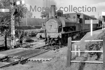 A Colonel Stephens light railway shot taken at Tenterden in 1946. The loco is Kent & East Sussex Railway Saddleback 0-6-0ST no. 4 which originated with the LSWR as no. 335 of the 330 class. No. 335 was the last of the first batch of six locos of this class built by Beyer Peacock in 1876. It was subsequently numbered 0335 on the LSWR's duplicate list and would survive beyond the 1923 grouping being exchanged ogether with some spares and two ex-LSWR carriages by the Southern Railway for the KESR's 0-8-0T Hecate and three ancient carriages in 1932 where it worked until withdrawal in 1948. [Mke Morant collection]