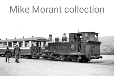 """This very rare original negative was taken at Campbeltown Quayside on the 2' 3"""" gauge Campbeltown & Machrihanish Light Railway. This undated view depicts one of the railway's two 0-6-2T's ARGYLL built for the line's opening in 1906 with works no. 1049. The sister engine ATLANTIC arrived in the following year. Equally of note in my opinion is the supremely elegant R. Y. Pickering built bogie passenger saloon which was one of six that comprised the line's entire passenger carrying capacity. Not evident in this slightly cropped version of the entire image is that this carriage is the entire consist which suggests that the shot was taken outside the tourist season. The railway was short lived closing to passenger traffic in May 1932 with both the 0-6-2T's being scrapped exactly two year later in May 1934. The passenger stock, however, gained a new lease of life as holiday homes at Trench Point where they survived until the 1950's with the last one being scrapped as late as 1958. [E. A. Gurney-Smith / Mike Morant collection]"""
