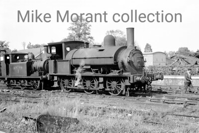 A Colonel Stephens light railway shot taken at Rolvenden in 1946. The loco is Kent & East Sussex Railway Saddleback 0-6-0ST no. 4 which originated with the LSWR as no. 335 of the 330 class. No. 335 was the last of the first batch of six locos of this class built by Beyer Peacock in 1876. It was subsequently numbered 0335 on the LSWR's duplicate list and would survive beyond the 1923 grouping being exchanged ogether with some spares and two ex-LSWR carriages by the Southern Railway for the KESR's 0-8-0T Hecate and three ancient carriages in 1932 where it worked until withdrawal in 1948. The second loco is Kent & East Sussex Railway former LBSCR Stroudley 'Terrier' 0-6-0T no. 3 which originated with the LBSCR as no. 70 being sold to the Rother Valley Railway in 1901. The RVR became the KESR in 1904 and no. 3 remained there until the line's closure in 1954 but was renumbered by BR in September 1949 to become 32670. This celebrity loco was withdrawn by BR in 1963 and is still with us today as a member of, appropriately, the heritage successor to the KESR. [Mke Morant collection]