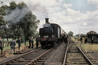 LCGB: The Eastern Counties Limited Rail Tour 12/7/59 Holden J69 class 0-6-0T no. 68566 at Stoke Ferry station which had closed to passenger traffic on 22/9/1930. No. 68566 had brought the tour train along the branch from Denver Junction but would  take it all the way to Kings Lynn on the return leg. [Mike Morant collection]