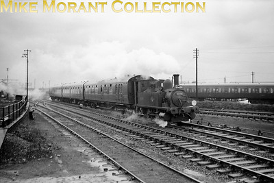 "LCGB: The ""B4"" Dock Tank Rail Tour (No.1) 9/3/63 Adams B4 dock tank No. 30096 is depicted here passing Eastleigh works and shed on the main line to Southampton. This relatively short trip started at Winchester Chesil, visited Ocean Terminal in Southampton, Eastleigh works and then terminated at Winchester City. 30096 had originally been named Normandy and would be named again when sold out of service to Corrall who named her Corrall Queen. In 1972 he was again sold on but this time to the Bulleid Pacific Preservation Society (later renamed The Bulleid Society) and the locomotive is, of course, now located on The Bluebell Railway."