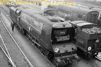 Bulleid original Merchant Navy pacific no. 35008 Orient Line sporting an Atlantic Coast Express headboard rests in the carriage sidings at Clapham Junction in the summer of 1956. This was a Summer Only roster for an Exmouth Jcn MN which hauled the 10.30 Ilfracombe - Waterloo (12.30 ex Exeter) and then worked the ECS of the 10.48 Torrington - Waterloo to Clapham Junction before running light to Nine Elms for the night. [Mike Morant]