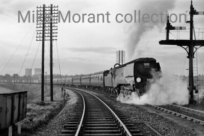 """RCTS/LCGB: North Midlands Rail Tour  11/5/63 Bulleid original West Country pacific No. 34006 Bude taking on water at Knighton South Curve. This tour wasn't the greatest of successes as 34006 allegedly let the side down with late running on both the Down leg from St. Pancras to Derby and the Up leg from Burton to St. Pancras but see the addendum below which is revealing. In any event, the visit to Derby works had to be by-passed as a result of the late running.  Harry Richardson has sent me the following from the horse's mouth so to speak:  """"I was the fieman on the return trip of this tour whilst my driver was Joe Smiddy and we were both stationed at Kentish Town Loco. Bude was in a wicked state. The coal wasn't up to main line work and my mate had lots of trouble with the steam reverser."""" [Mike Morant collection]"""