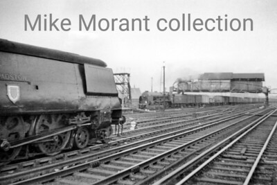 Bulleid original light pacific no. 34008 Padstow at Clapham Junction and a bit of luck plus, I suspect, some good judgement captures an unidentified Lord Nelson 4-6-0 entering the Windsor platforms with a lengthy freight train. Photo taken by Mike Morant