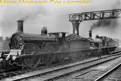 LBSCR Stroudley B1 0-4-2 No. 215 Salisbury and a 'G' class 2-2-2. A viewer informs me that they are standing on the spur points that take the locos onto a headshunt where they would have to reverse down the entrance line to Battersea loco yard. In other words, they are on the viaduct above the Battersea loco round houses.