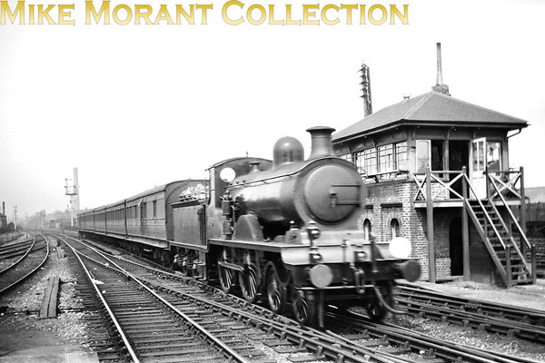 "LBSCR Richard Billinton designed B4 class 4-4-0 no. 59 approaches Hove station from the Worthing direction c. 1923/24. Built by Sharp, Stewart in September 1901 and named <i>Bagshot</i>, withdrawal would come as SR 2069 in August 1934. This is a post-grouping shot as the entire rake of rolling stock is of LSWR origin.<br> An observant viewer adds these notes regarding no. 59: <i>""The shape of the framing at either end was unique to this loco. It does not have the reverse curves seen on the rest of the class. This feature dates from the period when it ran with a Phoenix Smokebox Superheater (now removed). The tender appears to be in LBSC livery but it also seems to have an SR numberplate on the cab side. The lining visible on the driving wheel splasher suggests that the loco is still in LBSC umber livery. There were a few locos that appeared in a mixture of styles during the transitional period immediately after the grouping.""</i><br> [<i>Mike Morant collection</i>]"