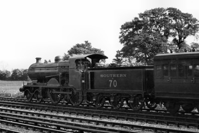 """LBSCR B4X class 4-4-0 No. B70 looks splendid in Southern lined green livery and it's a shame that we are unable to see this from the sunny side of the central subject. There was no date stated for this shot but it must have been taken before the number's 'B' prefix was removed in June 1931. The stated location is Basingstoke which seems to be an odd place to see an LBSCR locomotive in that era but it should be noted that the visible carriage is, in fact, an ex-LSWR one. B70 was one of Lawson Billinton's nominal rebuilds of the B4 class and this example entered service after the grouping in May 1924. On paper, at least, it survived in to BR ownership but never received its projected number, 32070 and according to my records seems to have spent almost all its time from nationalisation until withdrawal from service at New Cross Gate shed in August 1951 as a stored engine.  Peter Smart has suggested that this location simply doesn't fit the profile for Basingstoke but it's also interesting to read Chris Knowles-Thomas's notes regarding the B4X class in the early 30's: """"A number of B4Xs were repaired at Eastleigh from 1930 & B70 visiting the works in that year.  So that may explain the ex-LSWR location if, indeed, it is."""""""
