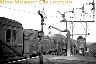 """Drummond M7 class 0-4-4T's 30052 and 30053 were tempoaririly transferred from Fratton to Faversham mpd in February and March 1953 respectively in order to provide a shuttle service between Faversham and Herne Bay following the catastrophic storm surges that left much of North Kent under water. Here we see 30053 (ironically) taking on water at Faversham station during the short period of the M7s' Kentish vacation. Both locos moved in the April to Brighton shed at the end of this stint. David Woodcock adds ........ """"Note the very unusual top-and-tail pull-and-push working, some, at least, of these trains had a 2-car pp-set plus a strengthener both fore and aft of the loco. There had been some similar (but usually shorter) workings between Brighton and West Worthing prior to electrification, and it probably happened on occasions elsewhere in conjunction with special events, but it certainly wasn't the SR pull-and-push norm."""" [Mike Morant collection]"""