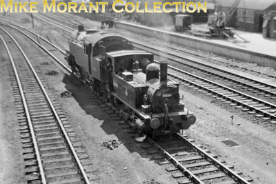 This shot was taken at the end of an Eastleigh Open Day but I don't recall which year it was. The star exhibit was Britannia 70004 William Shakespeare. Here we see ex-works Adams B4 0-4-0 dock tank no. 30094 propelling a dead standard 4MT 2-6-4T towards the works and shed area. Photo taken by Mike Morant