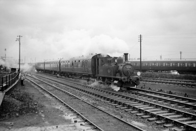 """LCGB: The """"B4"""" Dock Tank Rail Tour (No.1) 9/3/63 Adams B4 dock tank No. 30096 is depicted here passing Eastleigh works and shed on the main line to Southampton. This relatively short trip started at Winchester Chesil, visited Ocean Terminal in Southampton, Eastleigh works and then terminated at Winchester City. 30096 had originally been named Normandy and would be named again when sold out of service to Corrall who named her Corrall Queen. In 1972 he was again sold on but this time to the Bulleid Pacific Preservation Society (later renamed The Bulleid Society) and the locomotive is, of course, now located on The Bluebell Railway."""